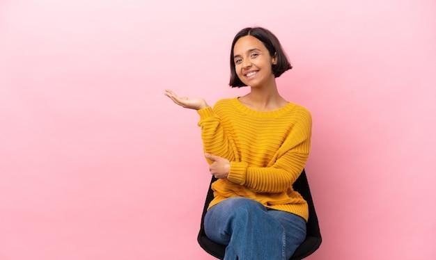 若い混血の女性が椅子に座り、手を横に伸ばして来るよう招待する