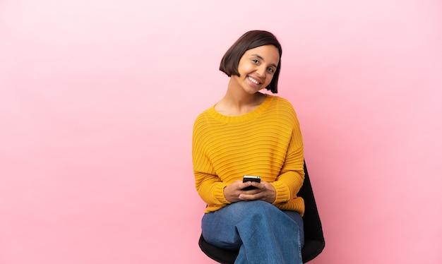 Молодая женщина смешанной расы, сидящая в изолированном кресле, отправляет сообщение с мобильного телефона