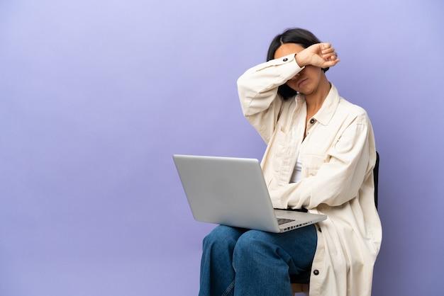 Молодая женщина смешанной расы, сидящая на стуле с ноутбуком, изолировала, закрывая глаза руками