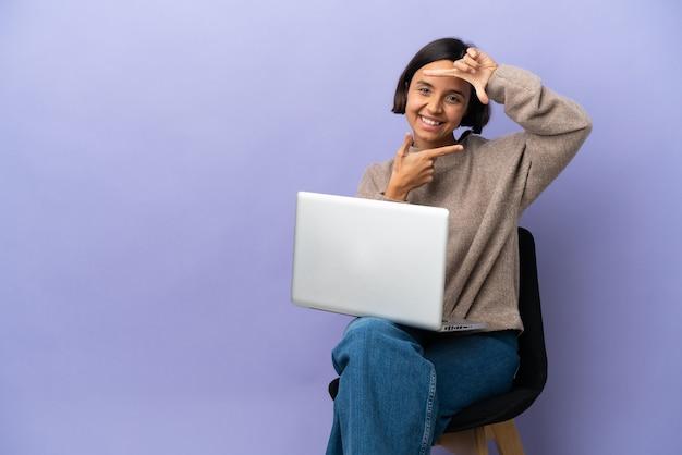 젊은 혼합 된 경주 여자 노트북 고립 된 초점 얼굴의 자에 앉아. 프레이밍 기호