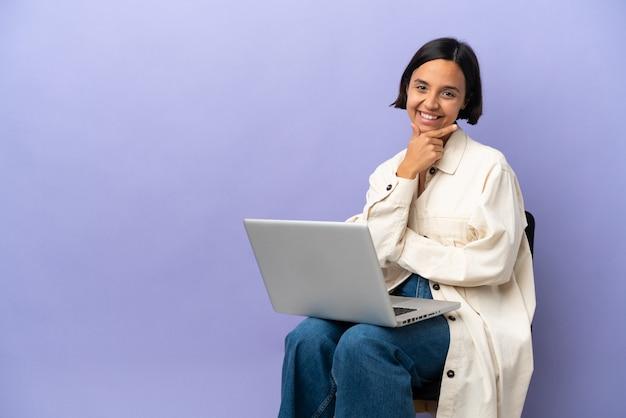 Молодая женщина смешанной расы, сидящая на стуле с ноутбуком, изолирована, счастливая и улыбающаяся