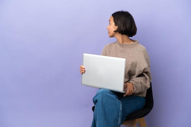 Молодая женщина смешанной расы сидит на стуле с ноутбуком, изолированным в заднем положении
