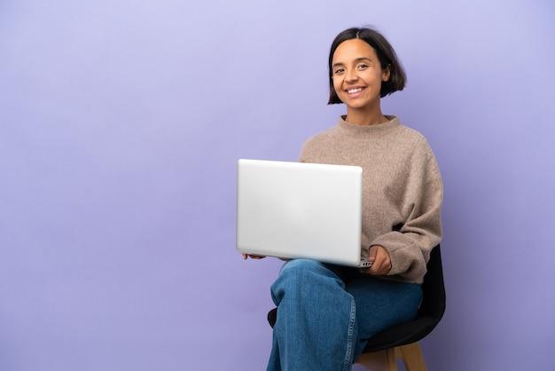 Молодая женщина смешанной расы, сидящая на стуле с ноутбуком, изолировала смех Premium Фотографии