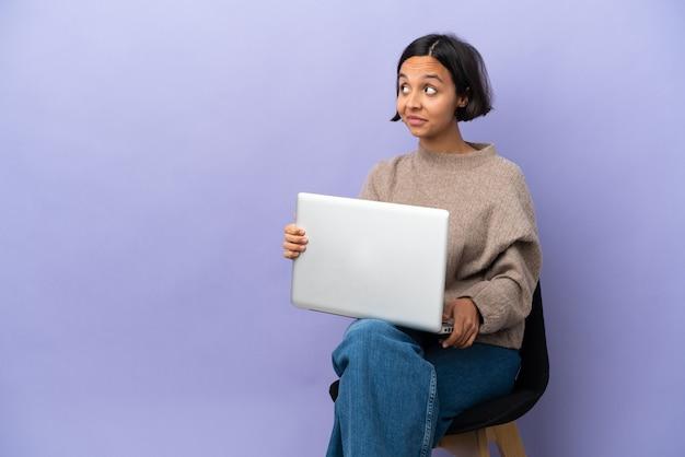 Молодая женщина смешанной расы, сидящая на стуле с ноутбуком, изолировала, делая жест сомнения, глядя в сторону