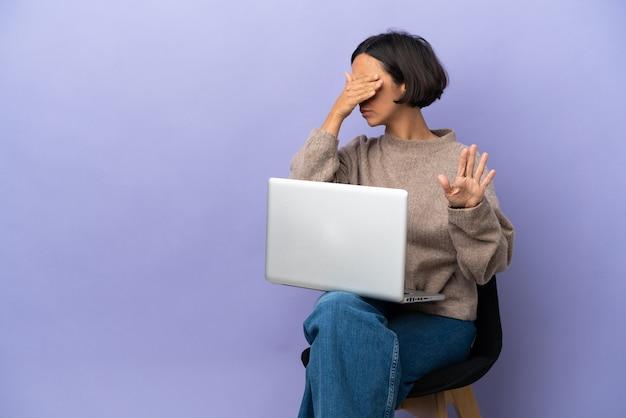 고립 된 노트북과 의자에 앉아 젊은 혼혈 여자 중지 제스처를 만들고 얼굴을 덮고