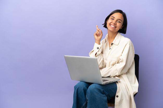 Молодая женщина смешанной расы, сидящая на стуле с ноутбуком, изолировала, показывая и поднимая палец в знак лучших