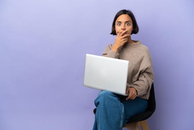 Молодая женщина смешанной расы, сидящая на стуле с ноутбуком, изолирована, удивлена и шокирована, глядя вправо