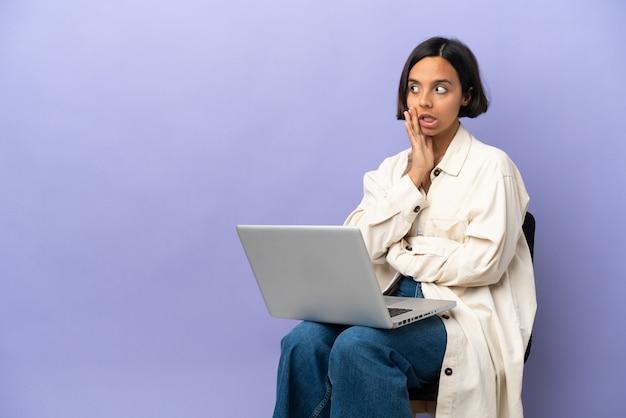 Молодая женщина смешанной расы, сидящая на стуле с изолированным ноутбуком