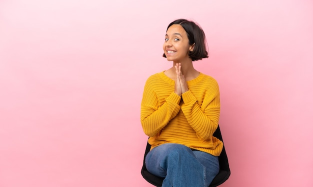 Young mixed race woman sitting on a chair isolated on pink background keeps palm together. person asks for something