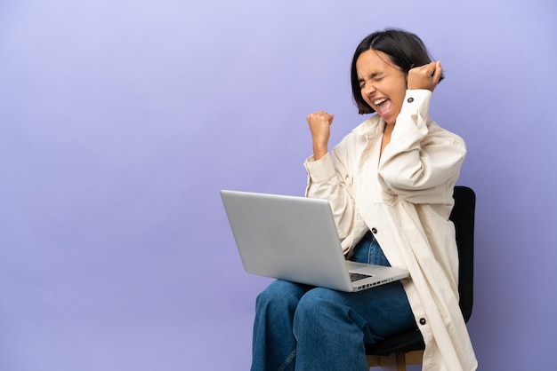 Young mixed race woman sitting on a chair with laptop isolated on purple background celebrating a victory