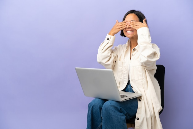 Young mixed race woman sitting on a chair with laptop isolated on purple background covering eyes by hands and smiling