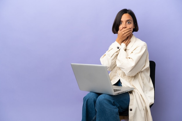Young mixed race woman sitting on a chair with laptop isolated on purple background covering mouth with hand