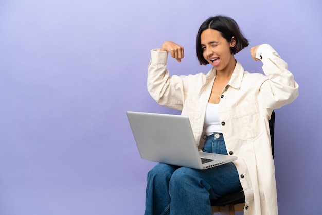 Young mixed race woman sitting on a chair with laptop isolated on purple background doing strong gesture