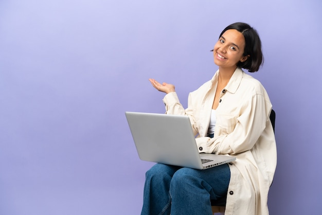 Young mixed race woman sitting on a chair with laptop isolated on purple background extending hands to the side for inviting to come