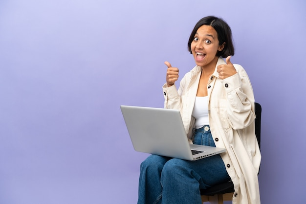 Young mixed race woman sitting on a chair with laptop isolated on purple background giving a thumbs up gesture