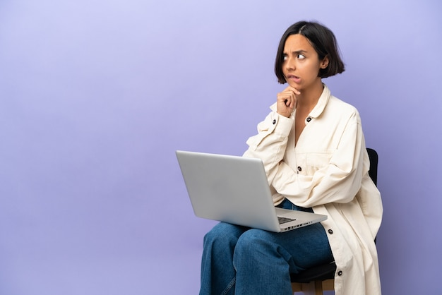 Young mixed race woman sitting on a chair with laptop isolated on purple background having doubts and thinking