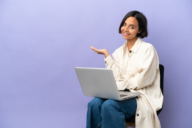 Young mixed race woman sitting on a chair with laptop isolated on purple background holding copyspace imaginary on the palm to insert an ad