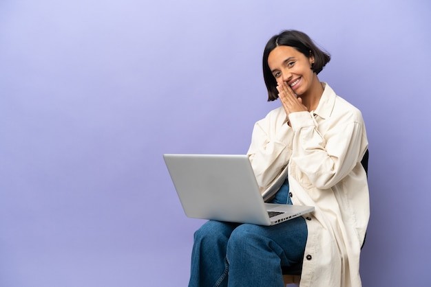 Young mixed race woman sitting on a chair with laptop isolated on purple background keeps palm together. person asks for something
