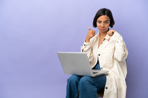 Young mixed race woman sitting on a chair with laptop isolated on purple background making good-bad sign. undecided between yes or not