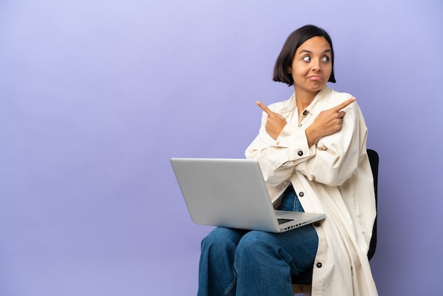Young mixed race woman sitting on a chair with laptop isolated on purple background pointing to the laterals having doubts