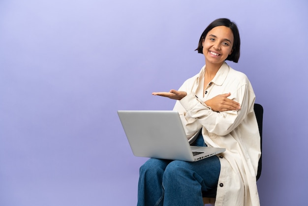 Young mixed race woman sitting on a chair with laptop isolated on purple background presenting an idea while looking smiling towards