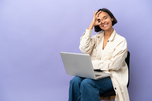Young mixed race woman sitting on a chair with laptop isolated on purple background showing ok sign with fingers