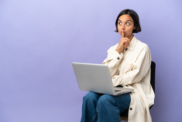 Young mixed race woman sitting on a chair with laptop isolated on purple background showing a sign of silence gesture putting finger in mouth