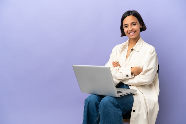 Young mixed race woman sitting on a chair with laptop isolated on purple background with arms crossed and looking forward