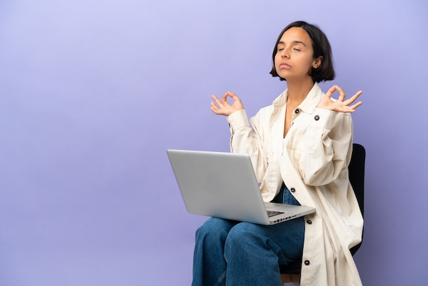 Young mixed race woman sitting on a chair with laptop isolated on purple background in zen pose