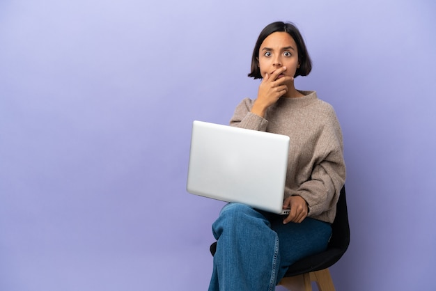 Young mixed race woman sitting a chair with laptop isolated surprised and shocked while looking right
