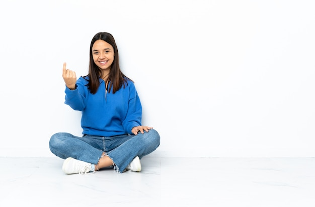 Young mixed race woman sitting on the floor isolated on white wall doing coming gesture