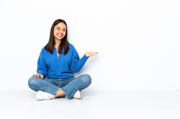 Young mixed race woman sitting on the floor on white wall extending hands to the side for inviting to come