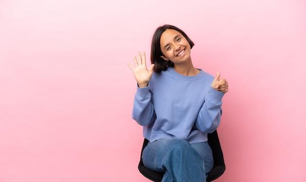 손가락으로 6 세 분홍색 배경에 고립의 자에 앉아 젊은 혼혈 여자