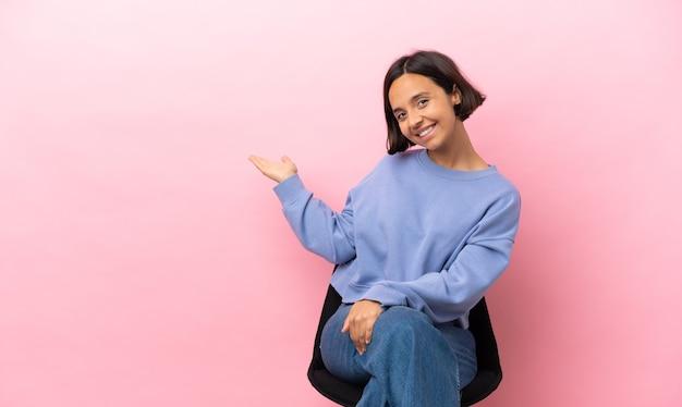 Молодая женщина смешанной расы сидит на стуле, изолированном на розовом фоне, протягивая руки в сторону, приглашая приехать
