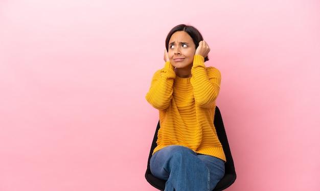 좌절과 귀를 덮고 분홍색 배경에 고립 된 의자에 앉아 젊은 혼혈 여자