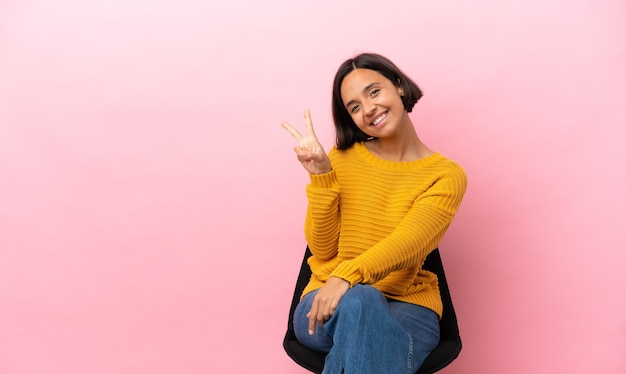 Молодая женщина смешанной расы сидит на стуле, изолированном на розовом фоне, счастлива и считает три пальцами