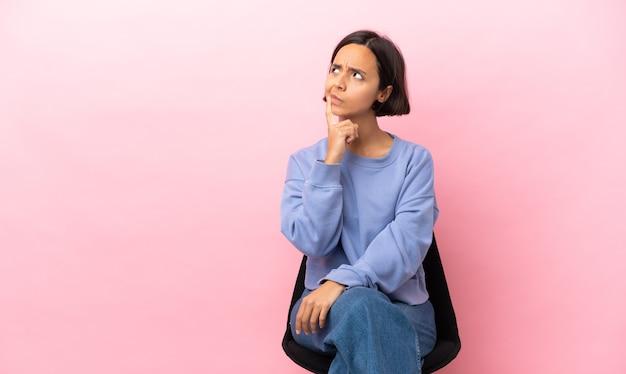 찾는 동안 의심을 갖는 분홍색 배경에 고립의 자에 앉아 젊은 혼합 된 경주 여자
