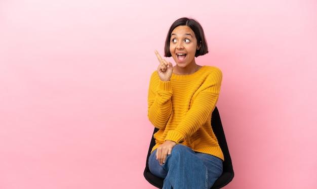 분홍색 배경에 고립 된 의자에 앉아 젊은 혼혈 여자는 손가락을 들어 올리는 동안 솔루션을 실현하려는 의도