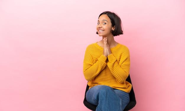 ピンクの背景で隔離の椅子に座っている若い混血の女性は、手のひらを一緒に保ちます。人は何かを求めます