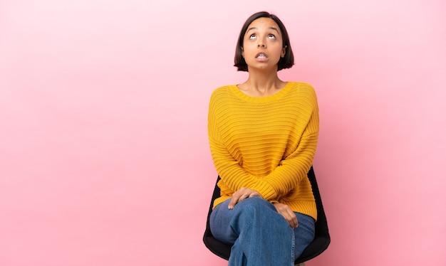 ピンクの背景に分離された椅子に座って見上げると驚きの表情で若い混血の女性