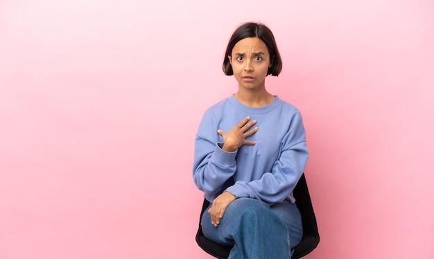 자신을 가리키는 분홍색 배경에 고립의 자에 앉아 젊은 혼혈 여자