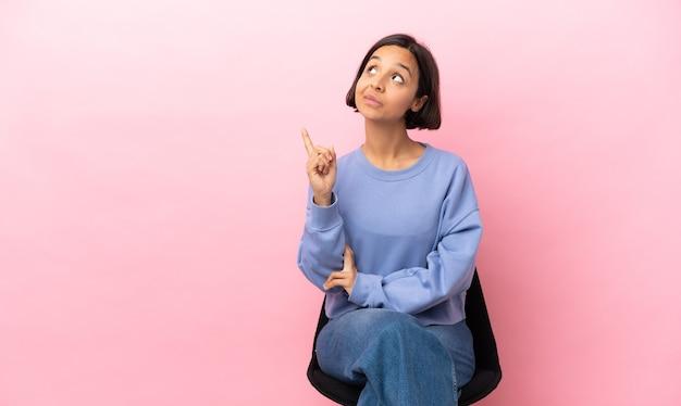 素晴らしいアイデアを指しているピンクの背景に分離された椅子に座っている若い混血の女性