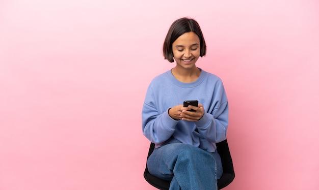 Молодая женщина смешанной расы сидит на стуле, изолированном на розовом фоне, отправляет сообщение с мобильного телефона