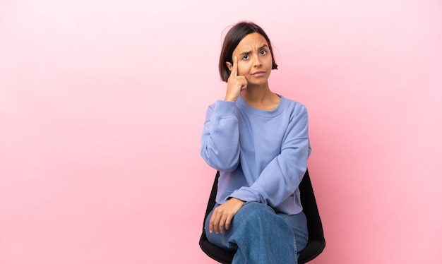 アイデアを考えてピンクの背景に分離された椅子に座っている若い混血の女性