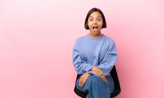 Молодая женщина смешанной расы сидит на стуле, изолированном на розовом фоне с удивленным выражением лица