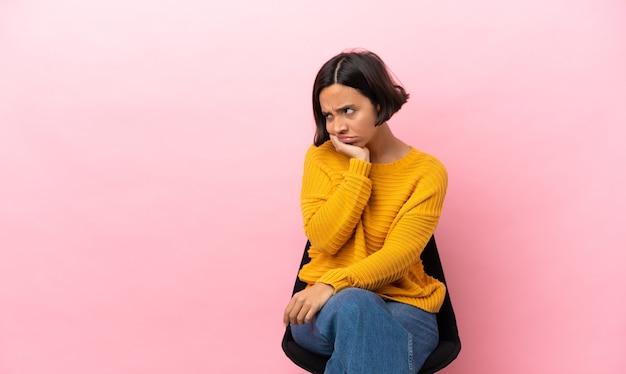 Молодая женщина смешанной расы сидит на стуле, изолированном на розовом фоне, с усталым и скучающим выражением лица