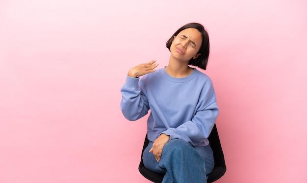 Молодая женщина смешанной расы сидит на стуле, изолированном на розовом фоне с усталым и больным выражением лица
