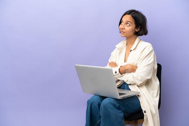 Молодая женщина смешанной расы сидит на стуле с ноутбуком, изолированным на фиолетовом фоне и смотрит вверх