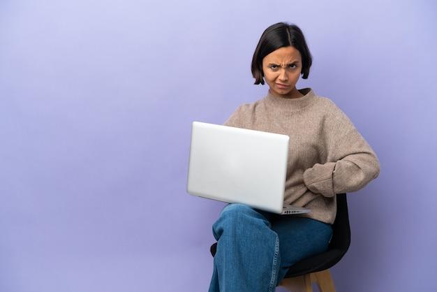 Молодая женщина смешанной расы, сидящая на стуле с ноутбуком, изолирована на фиолетовом фоне в гневе