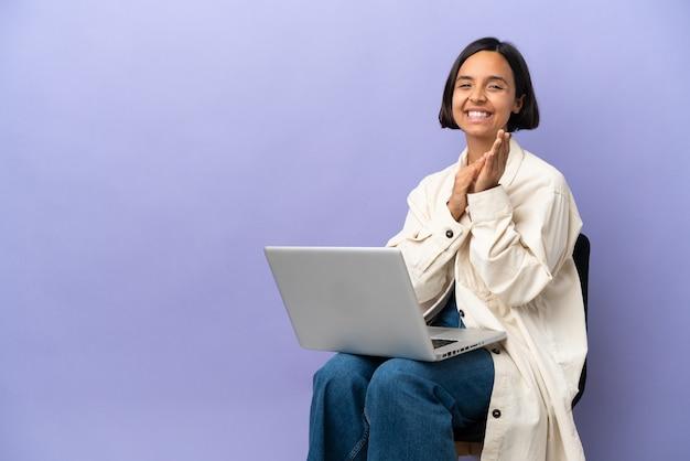 Молодая женщина смешанной расы сидит на стуле с ноутбуком, изолированным на фиолетовом фоне, аплодирует после презентации на конференции